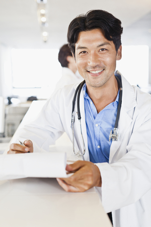 Doctor smiling with folder in hallway