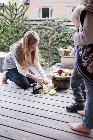 Girl peeling fruit on patio LANG_EVOIMAGES