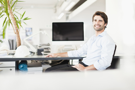 enthusiastically: Businessman smiling at desk LANG_EVOIMAGES