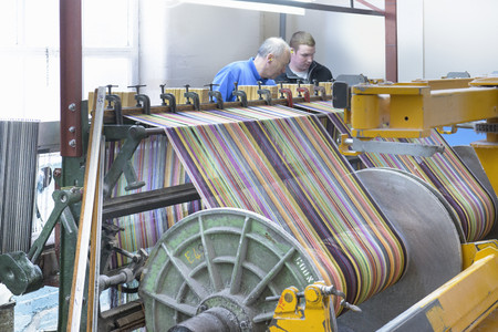 weavers: Worker using looms in textile mill