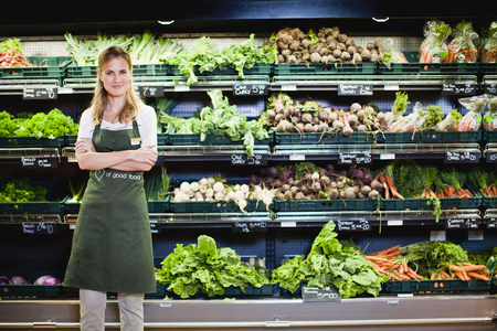 three shelves: Grocer smiling in produce section