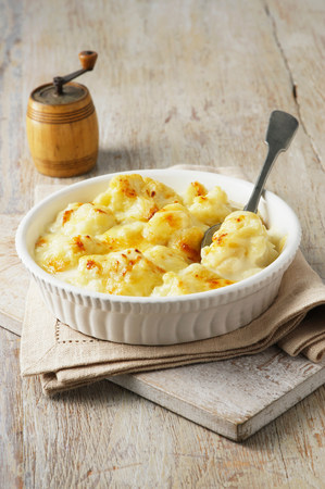 flavouring: Cauliflower cheese in large bowl with spoon and wooden pepper grinder