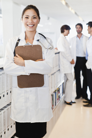 Smiling doctor holding clipboard LANG_EVOIMAGES