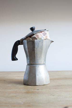 Coffee pot full of money on desk LANG_EVOIMAGES