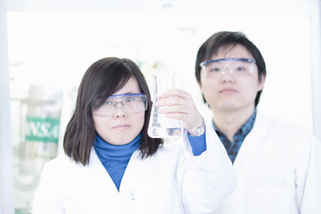 somber: Scientists examining liquid in lab