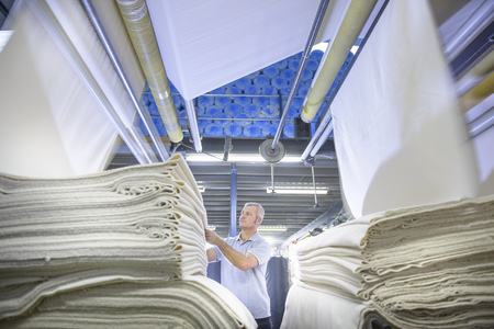 Worker examining fabric in textile mill