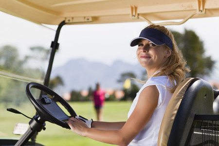 transportation: Woman driving golf cart on course