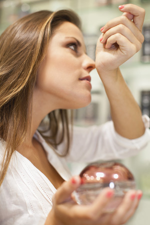 indecisive: Woman trying on fragrances in store