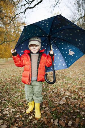 mischievious: Boy in rain boots and umbrella in park