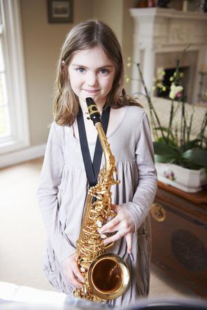 Smiling girl playing saxophone LANG_EVOIMAGES