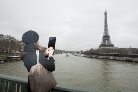 histories: Woman taking picture with tablet