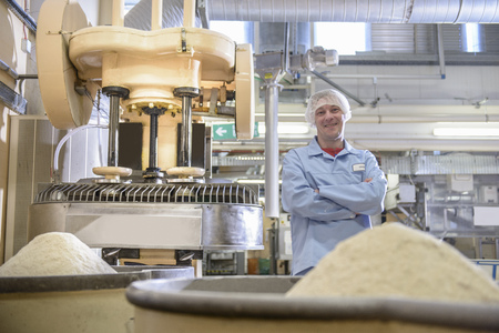 proudly: Worker with machinery in biscuit factory