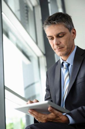 通信: Mature businessman using digital tablet