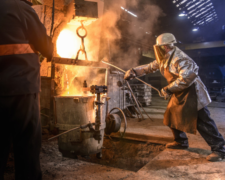in twos: Worker pouring molten metal in foundry