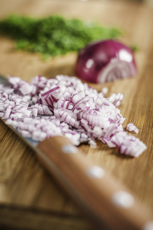 enclose: Close up of knife and chopped onions