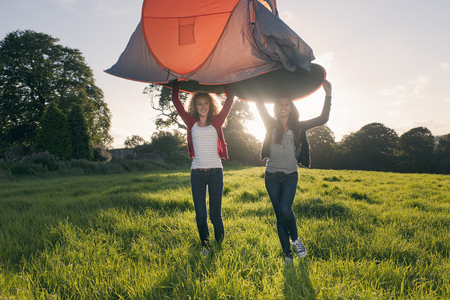 arms lifted up: Teenage girls pitching tent in field