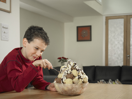 preadolescent: Boy eating large bowl of ice cream