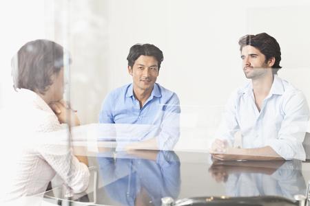 通信: Business people viewed through window