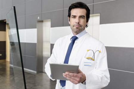 somber: Doctor using tablet computer LANG_EVOIMAGES