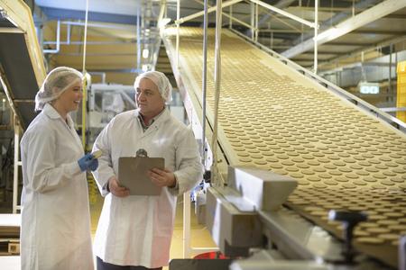 通信: Workers talking in biscuit factory LANG_EVOIMAGES