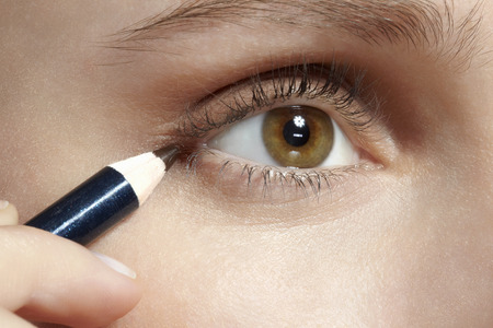 applied: Close up of woman applying makeup LANG_EVOIMAGES