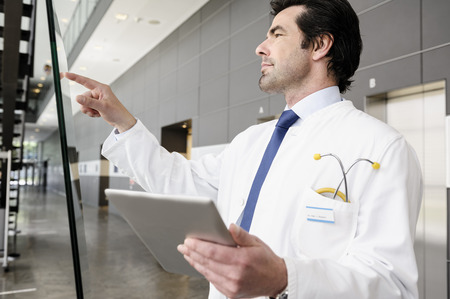 power operated: Doctor pointing to glass panel LANG_EVOIMAGES