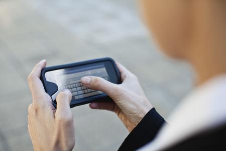 reconocimientos: Empresaria utilizando teléfono celular al aire libre LANG_EVOIMAGES