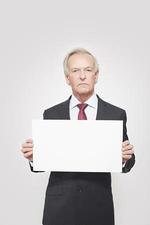 frowns: Businessman holding blank card LANG_EVOIMAGES
