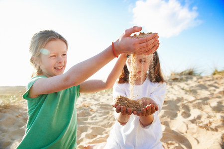joyous: Two girls playing with sand