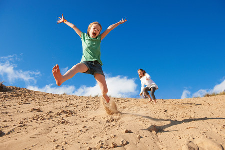 impulsive: Two girls jumping on beach LANG_EVOIMAGES