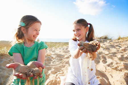 travel features: Two girls playing with sand