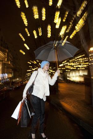 drizzling rain: Woman under umbrella on city street