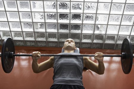 somber: Man lifting weights in gym