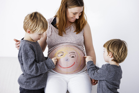 Children drawing on pregnant mother