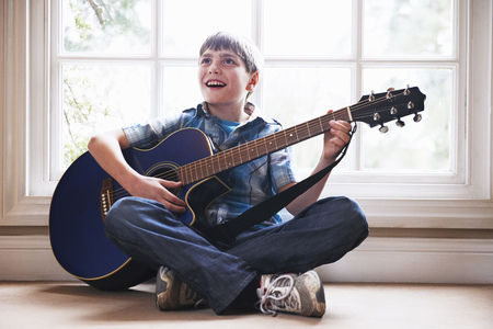 a rehearsal: Boy playing guitar on floor