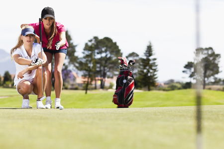 Women playing golf on course LANG_EVOIMAGES