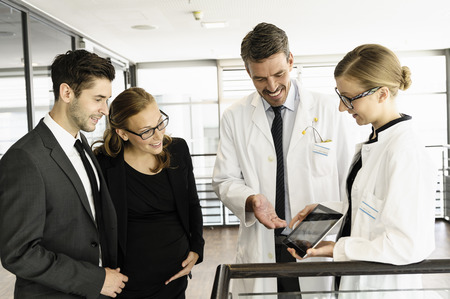 power operated: Doctors and business people with tablet LANG_EVOIMAGES