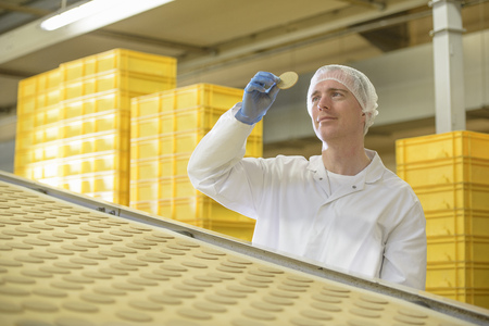 assessed: Worker examining biscuit in factory