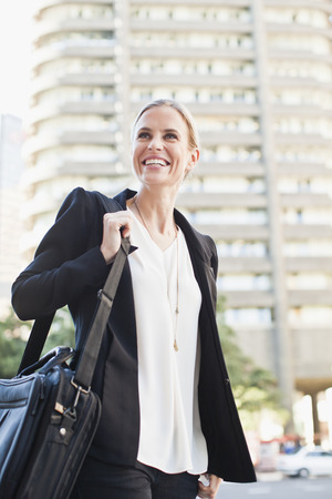 Businesswoman carrying briefcase outdoors