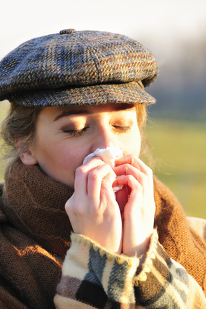 sickly: Woman blowing her nose at sunrise