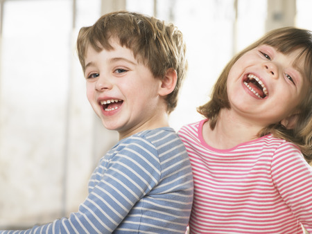 in twos: Children smiling together indoors