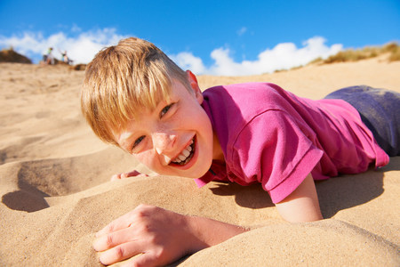 Blonde haired boy lying on beach LANG_EVOIMAGES