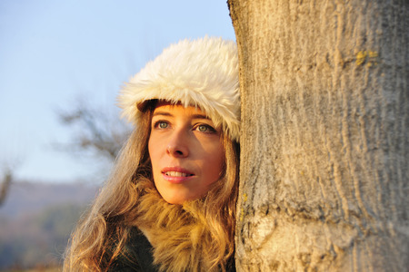 Woman in fur hat hiding behind tree LANG_EVOIMAGES