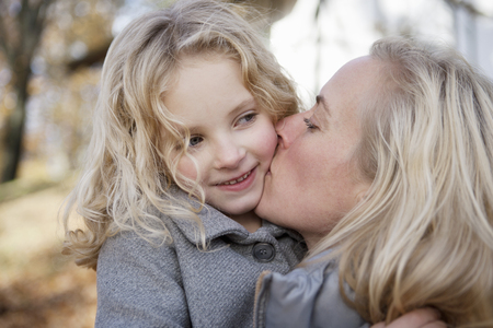 smooching: Mother kissing daughter outdoors LANG_EVOIMAGES