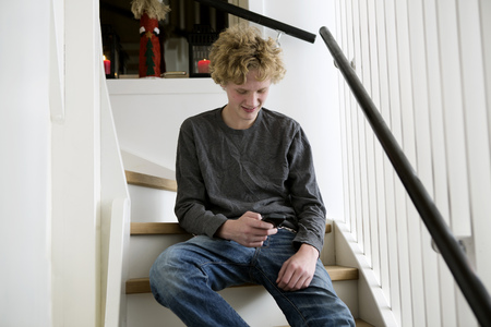 responding: Teenage boy using cell phone on stairs