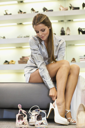 Woman trying on shoes in store LANG_EVOIMAGES
