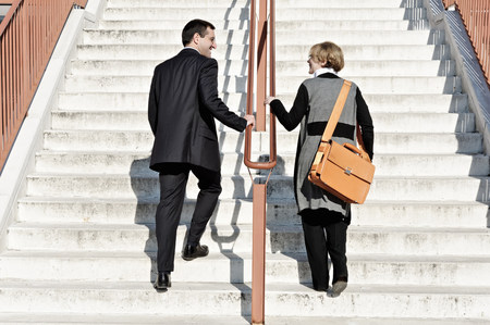 team from behind: Businesswoman and man ascending staircase,outdoors