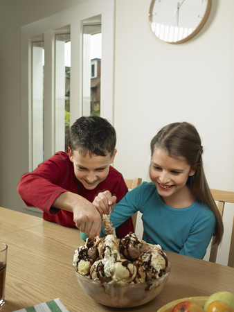 eagerly: Children eating large bowl of ice cream LANG_EVOIMAGES