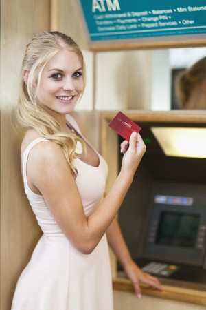 withdrawal: Smiling woman using ATM