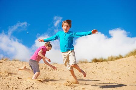 Two boys running down sand dune LANG_EVOIMAGES